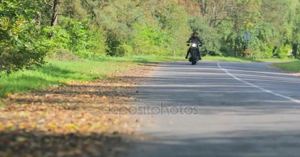 4 k žena jízda café-racer vlastní motocykl světlometů na podzimní příroda sunny štěrková cesta stromů. Biker dívka jednotky k fotoaparátu pomalu za nimi. Motocyklistů zařízení bezpečnosti a rychlosti pravidla silničního provozu