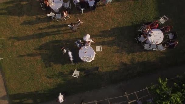 Nízký let střílel nad lidem, kteří sedí u stolu na zelený trávník na průchodné bbq piknik párty v zobrazení nejvyšší slunce venku restauraci nebo kavárně. Místní jídlo a Víno ochutnávání svátek festival v Evropě
