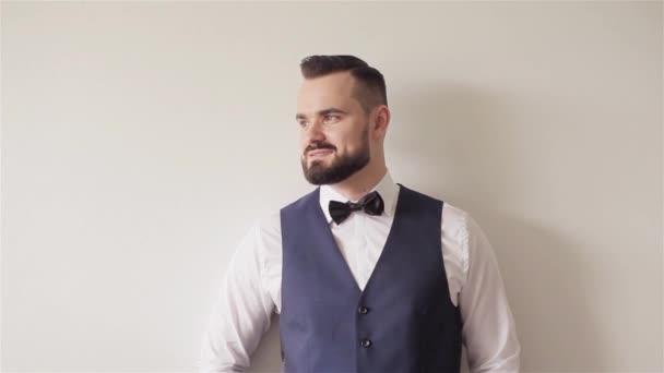 30-as években portréja szakállas férfi áll pózol: a fehér falra néz ki, a kamera mosolyogva értékesíti. Zselés haj fodrász shop kliens. Megjelenés ruházat ruházat kiegészítők és klasszikus férfi divat-részletek