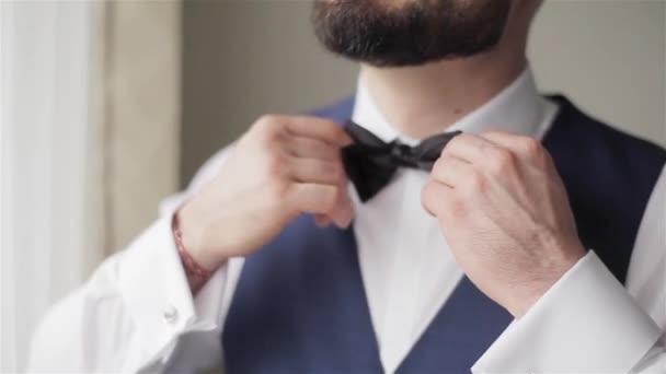 Vousatý muž upraví Černý motýlek closeup spěchal Připravte pro ODS headshot bez tváře. Pohledný ženich v bílé košili vesta se ráno budí strach, kontrola klasický vzhled pro svatební obřad