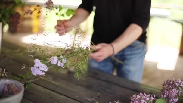 Ruce kytici z letní kytice zblízka na dřevěný rustikální stůl malá hloubka ostrosti. Květinářství v práci přípravy květinové kompozice čelní pohled. Květinářství přírodní ekologické životní styl