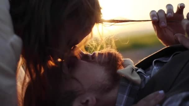 Happy couple having intimate moment of closeness together outdoors backlit sunset slow motion close up. Young woman kissing mens face eyes lips lying in festive clothes evening golden light nature