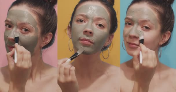 Triple portrait of young woman simultaneously applying clay mask on face with brush indoors. Front view of three girls taking skin care using facial cleansing cosmetics on colorful isolated background