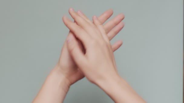 Detailní záběr tleskání ženských rukou izolovaných na modrošedém pozadí kopírovat textový prostor. Žena bez tváře tleskající uvnitř makro dlaně zpomaluje. Značky jazyků těla