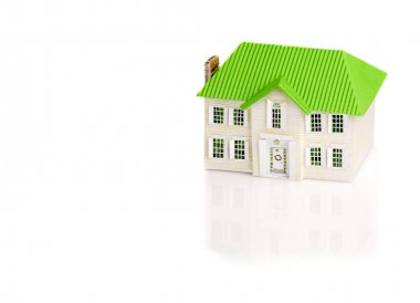 A toy house with a green roof on a white background