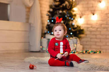 little baby girl posing in studio in costume with christmas deco