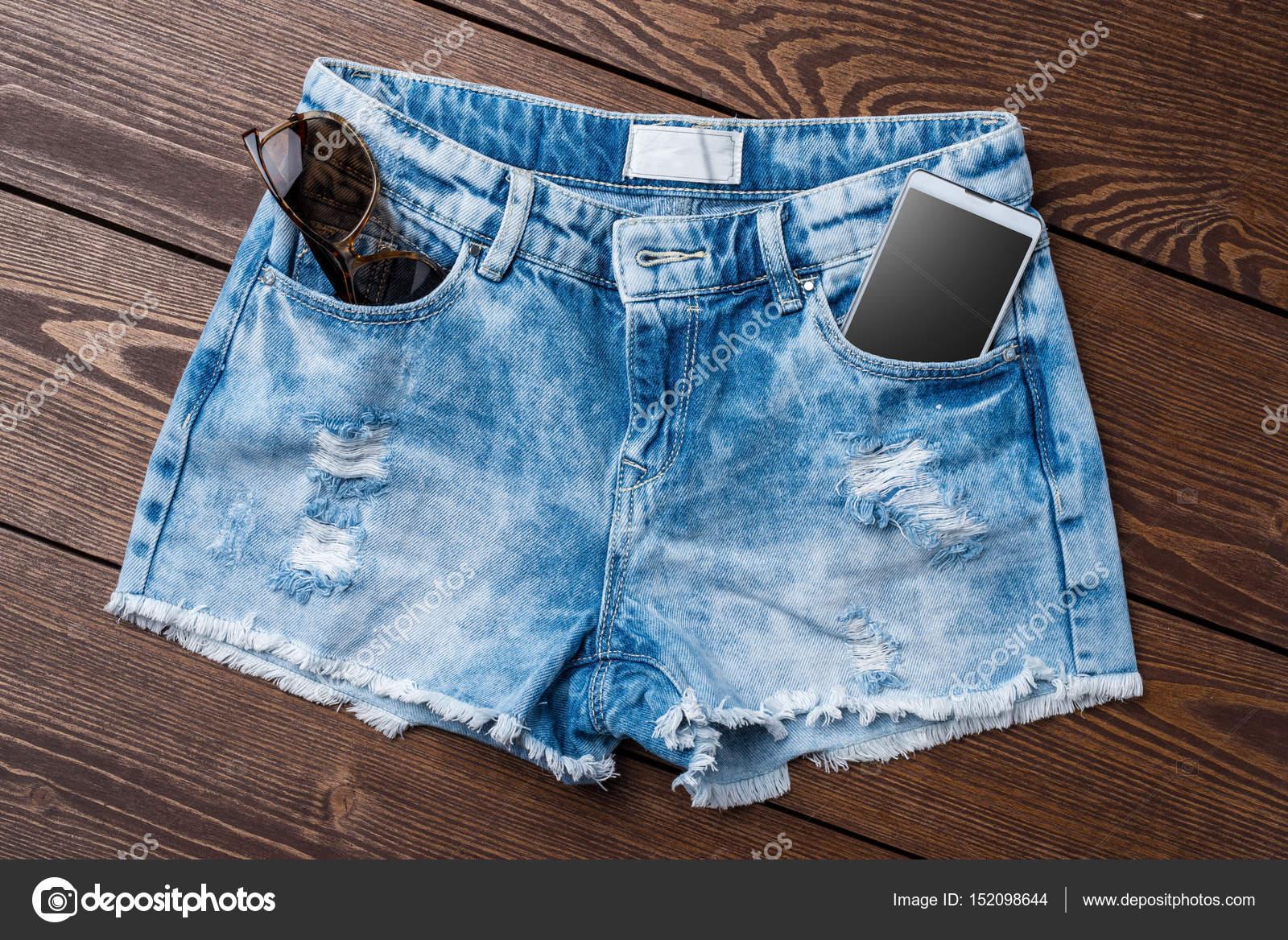 905797ea82 Pantalones cortos de jeans de mujer en mesa de madera — Fotos de Stock