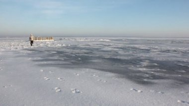 Man in a in a beige sweater running across the ice of a frozen river, Ob Reservoir, Russia