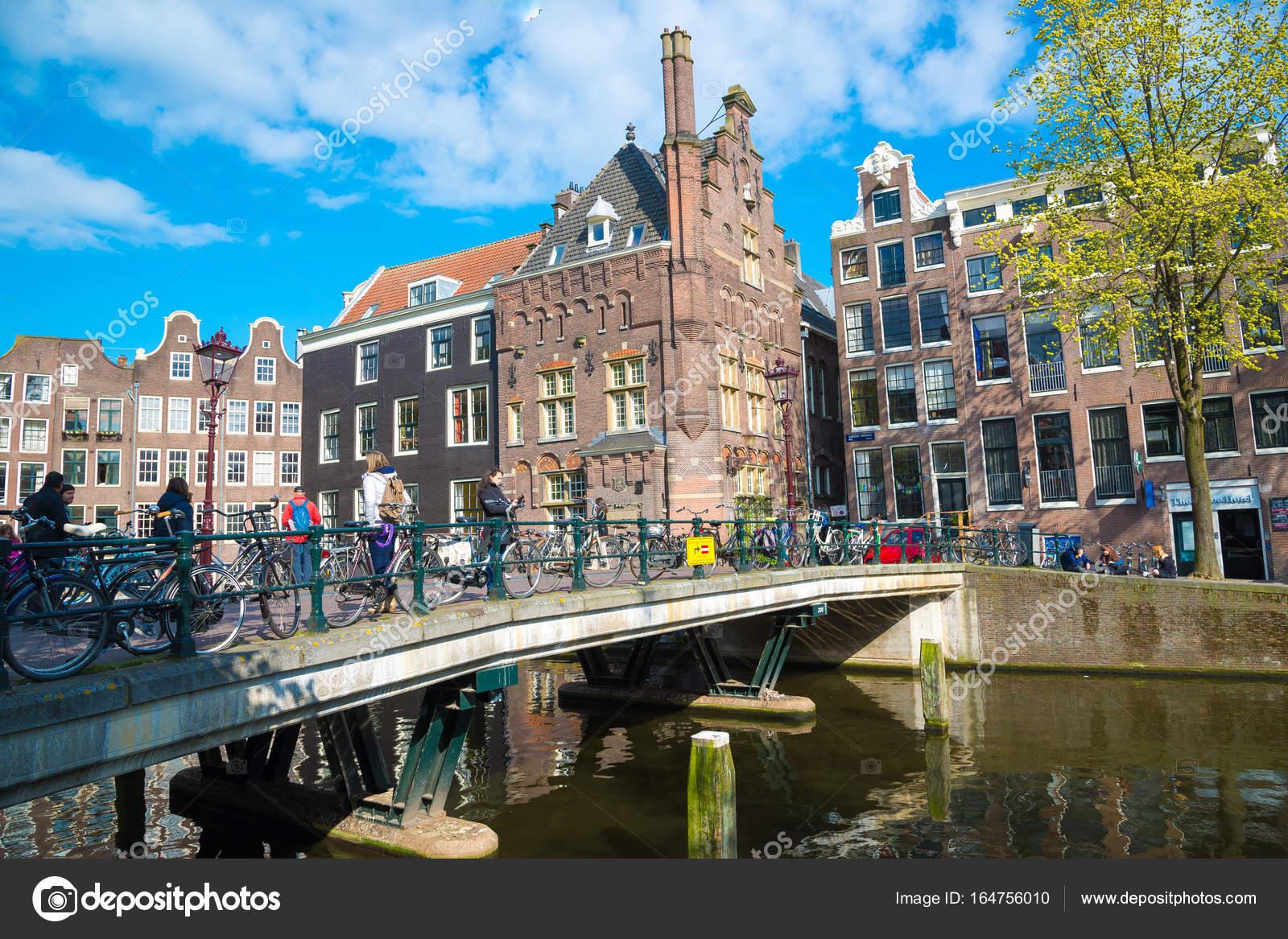 I turisti a piedi su un vecchio ponte in pietra nel centro for Centro di amsterdam