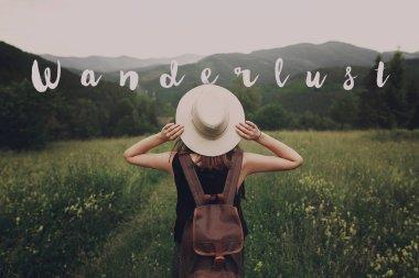 hipster traveler woman holding hat