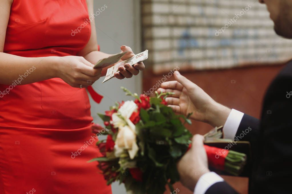 groom paying for bride to bridesmaid