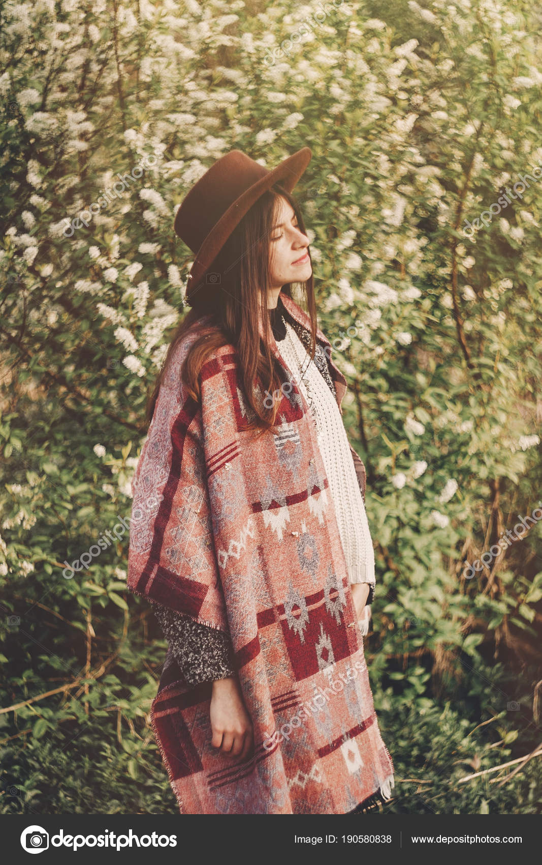 Chica hipster estilo de sombrero y poncho con la situación de un cabello  hermoso parque en sol de noche. viajero mujer moda ropa relajante en el  jardín de ... 844b357b2480