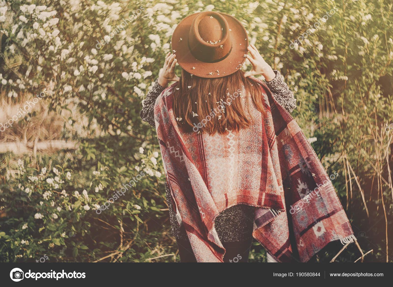 Chica hipster estilo de sombrero y poncho con un cabello hermoso con flores  caminando en el Parque sol de noche. la parte posterior del viajero de la  mujer ... f6b73d91d7c1
