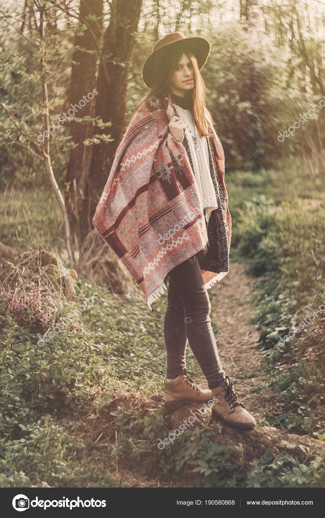 Chica hipster estilo de sombrero y poncho posando en el bosque en sol de  noche. viajero de moda mujer en luz del sol. espacio para texto. momento ... f584fa0a817a