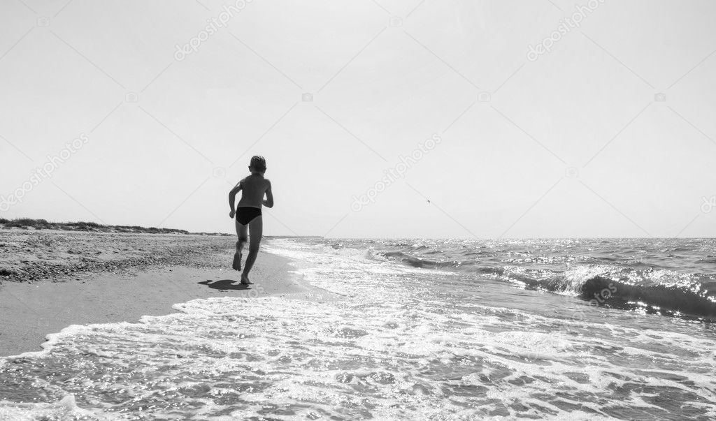 Boy running on the sea. Monochrome colors