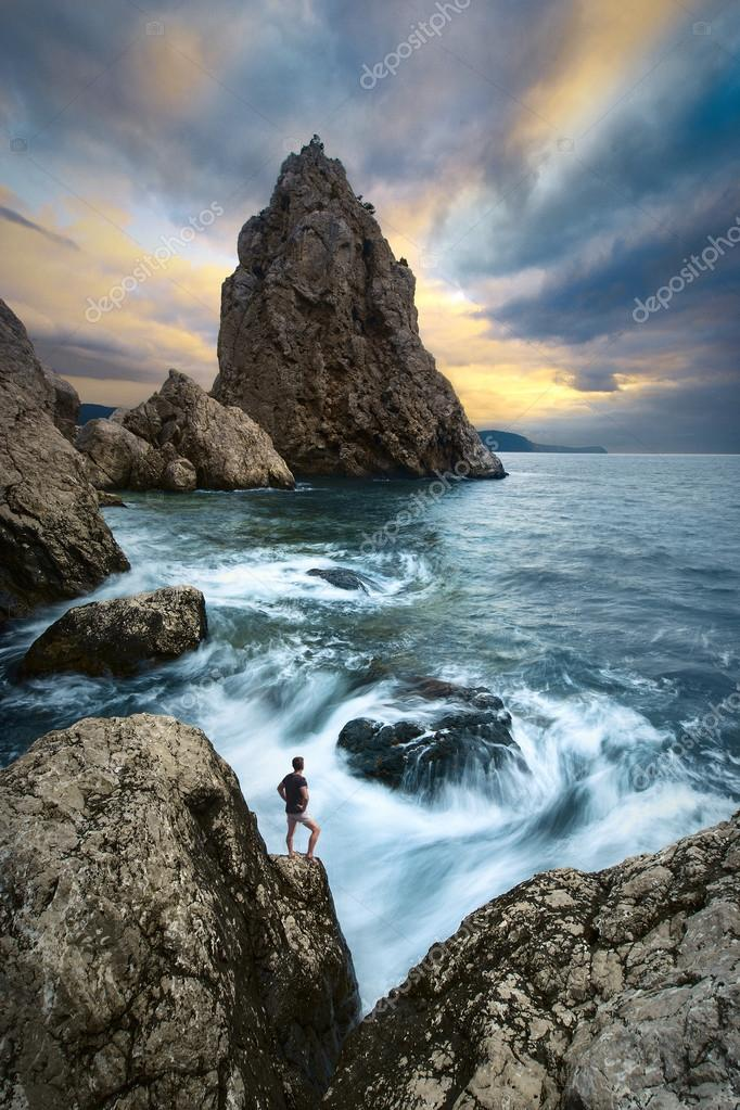 Man on a cliffs edge above the sea