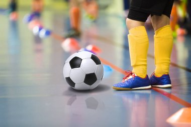 Children training soccer futsal indoor gym. Young boy with soccer ball training indoor football. Little player in yellow sports socks