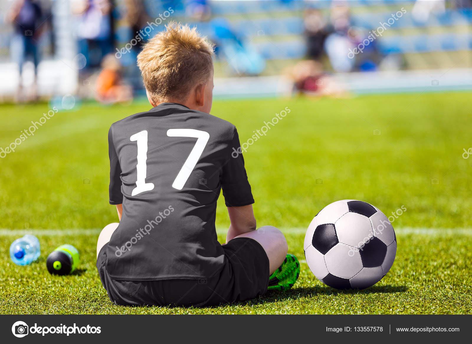 c919ae1b354f6 Criança no sportswear preto com bola de futebol. Menino sentado no campo de  futebol.