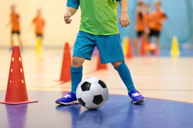 Football futsal training for children. Soccer training dribbling cone drill. Indoor soccer young player with a soccer ball in a sports hall. Player in blue uniform. Sport background.