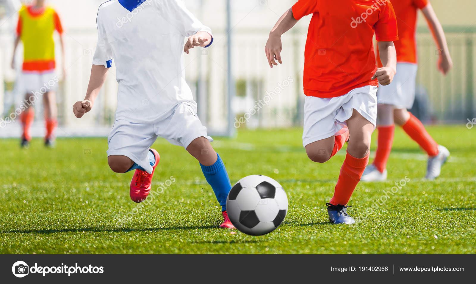 f83236464 Kolejny piłkarski młodych piłkarzy. Piłkarze kopanie piłki nożnej mecz gra. Piłka  nożna juniorów uruchomiona po piłkę. Stadion piłkarski w tle.