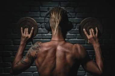 Back of athletic young aesthetic man listening music