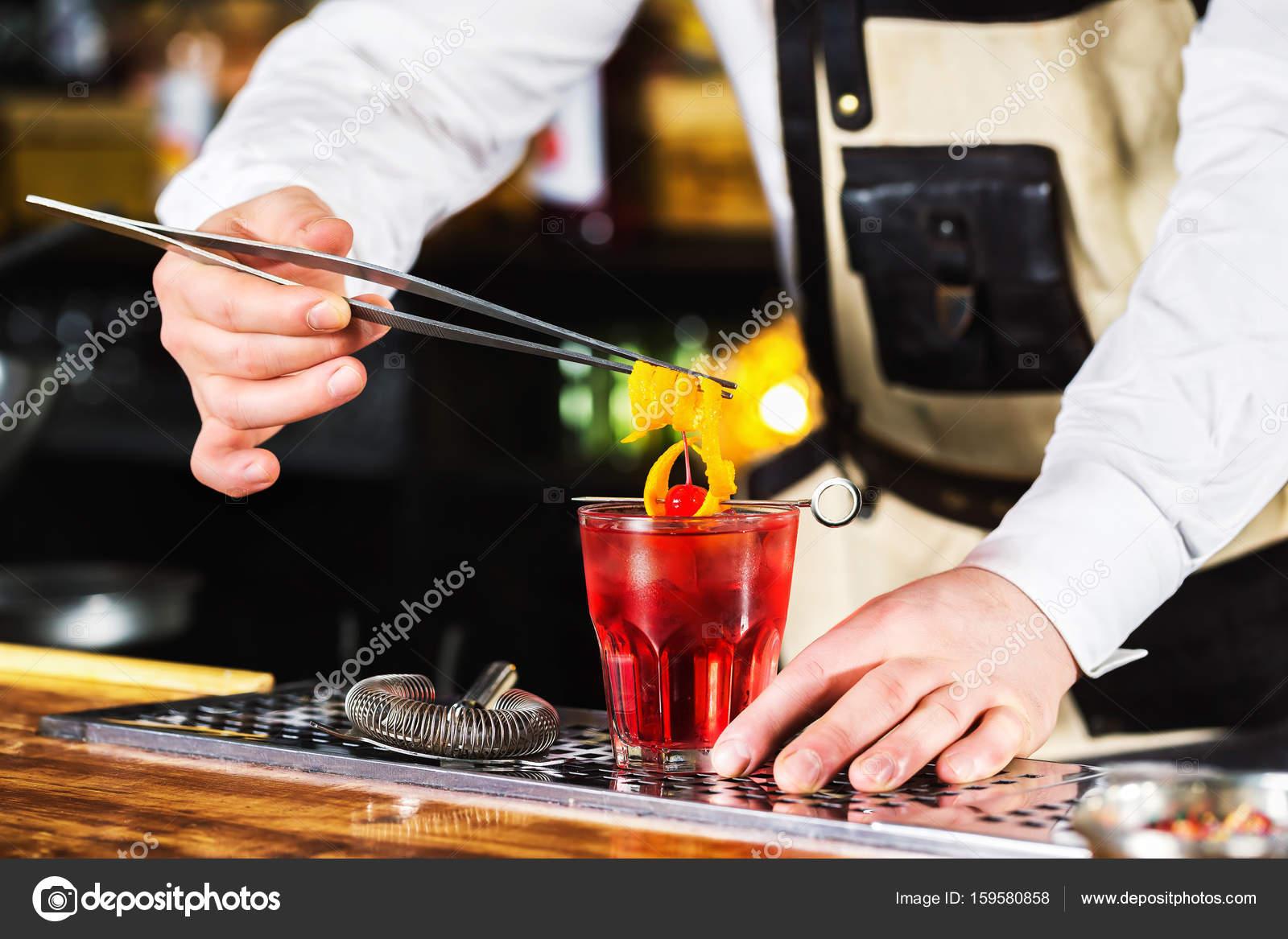 Barkeeper Hält Orangenschale In Zange Dekoration Rot Cocktai