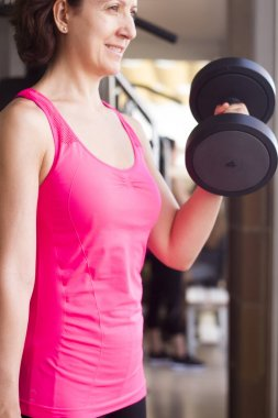 Girl doing exercise with 4 kg weights in the gym