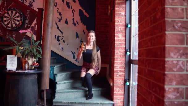 Mädchen steigt Stufen hinauf, geht mit einem Glas Bier voran