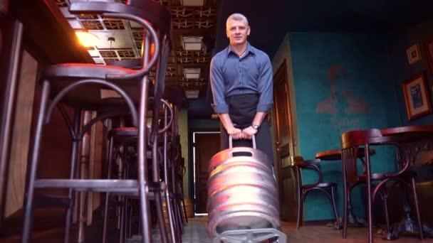 Ein Barkeeper mit einem Fass Bier auf dem Boden