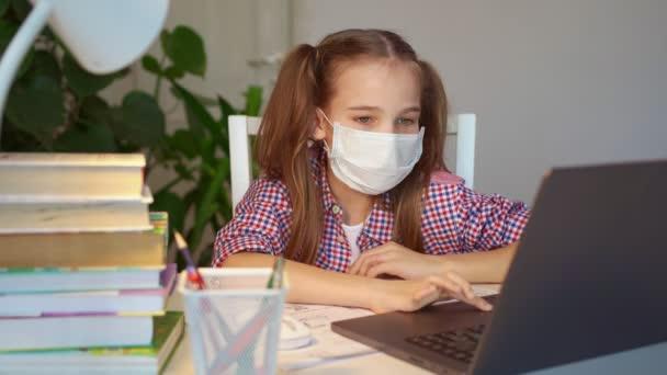 iskolai lány orvosi maszk hallgat leckét laptop