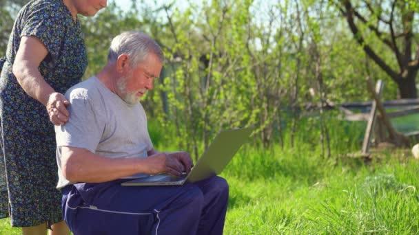 Ältere Männer und Frauen mit Laptop im Dorf