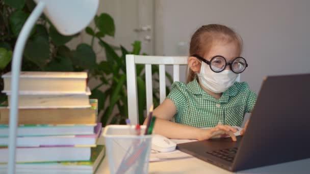 Kind in Maske mit Brille lernt Fernbedienung am Laptop