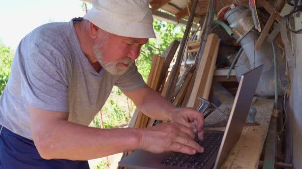 Älterer Mann arbeitet mit Laptop im Dorf