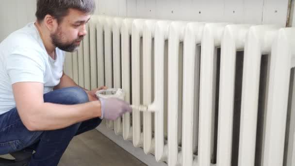 Mann mit Handschuhen streicht Heizkörper in Wohnung