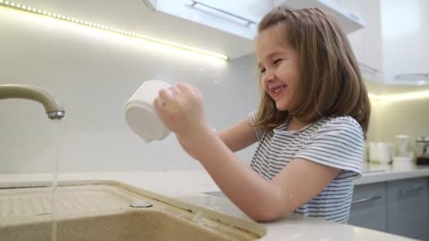 fröhliches kleines Mädchen spült das Geschirr.