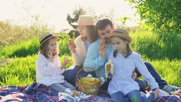 rodiče s dcerami na pikniku na trávníku jedí ovoce a croissanty