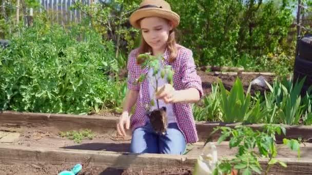 attraktive Teenie-Mädchen mit Hut arbeitet mit einer Harke. ein junger Bauer.