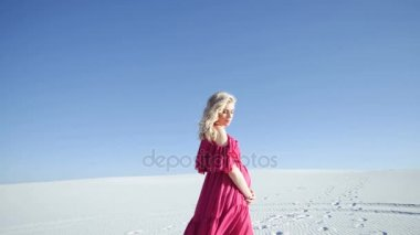A woman walking on a sand dune during sunrise