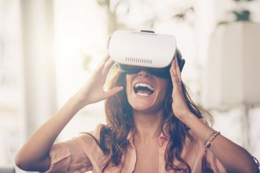 Amazed woman looking in a VR goggles and gesturing