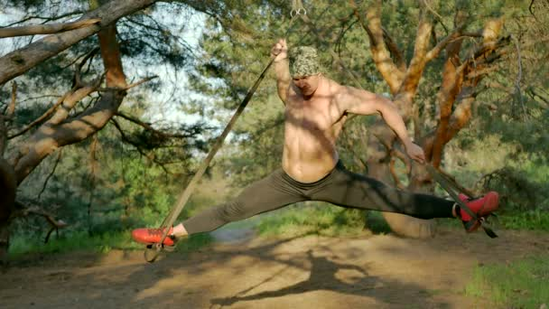 The athlete makes stretching on the ropes in the forest
