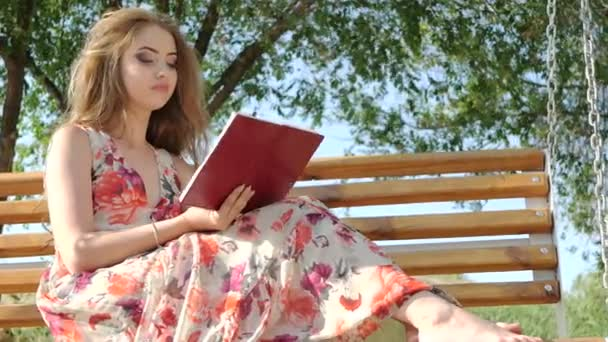 Mädchen mit einem Buch auf einer Bank im Park