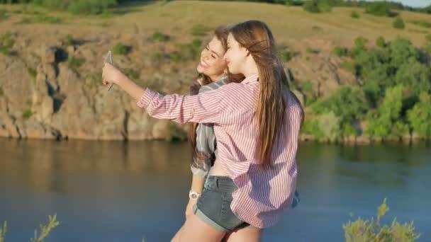 Closeup bezstarostné mladistvých dívek dělat legrační obličeje a úsměvu pro selfie.