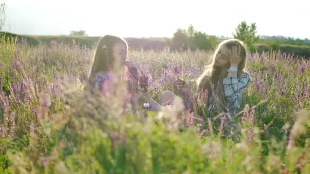 Děvčata sedí na poli s fialovými květy