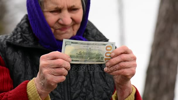Holding a pénz a kezében öregasszonyt ellenőrzi a hitelességét. Idős asszony ellenőrzési dollárt pénz
