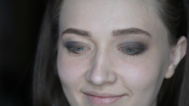 Vizážistka, líčení na modelčiny oči s kosmetickým vybavením. Dekorativní kosmetika očí.