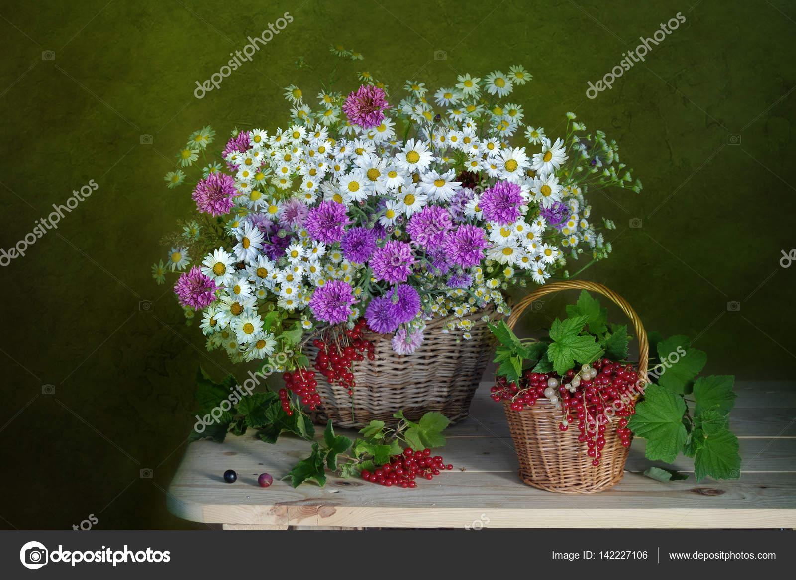 Полевые цветы и спелых, красные ягоды в корзине ...