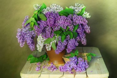 Still life a bouquet of lilacs in a vase on a brown background.