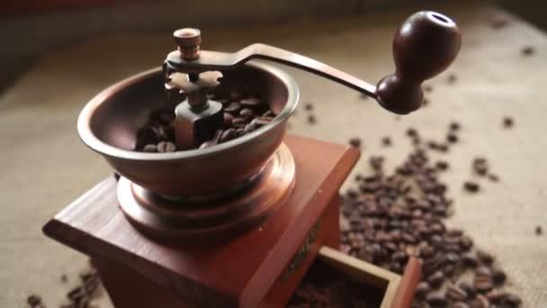 Kávová zrna a starý mlýnek na kávu. Posouváním kamery