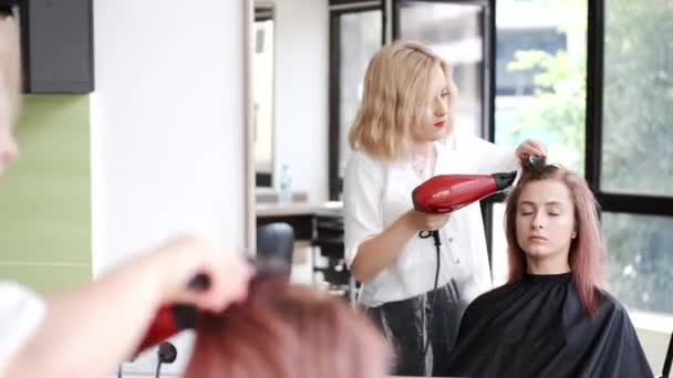 Hairdresser drying clients hair using red hair dryer