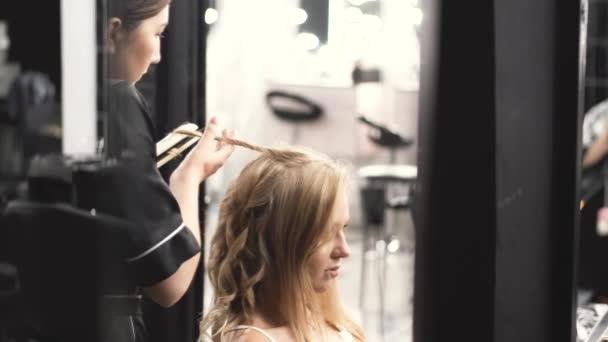 Kadeřník v černé uniformě curling blond vlasy v salonu